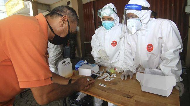 Dua petugas medis menyaksikan seorang warga memotret hasil tes diagnostik cepat atau rapid test COVID-19 miliknya di Sungai Raya Dalam, Kabupaten Kubu Raya, Kalimantan Barat, Kamis (14/5/2020). Hingga Rabu (13/5/2020) dari hasil rapid test yang digelar Dinas Kesehatan Provinsi Kalbar di wilayah Kalbar tersebut terdapat 20.665 warga yang Non Reaktif dan 1.188 warga yang Reaktif. ANTARA FOTO/Jessica Helena Wuysang/nz