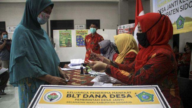 Warga saat menerima uang Bantuan Langsung Tunai (BLT) dana desa di Balai desa Janti, Waru, Sidoarjo, Jawa Timur, Kamis (14/5/2020). Bantuan langsung tunai (BLT) dari pemerintah melalui Kementerian Desa, Pembangunan Daerah Tertinggal, dan Transmigrasi  sebesar Rp600 ribu perbulan selama tiga bulan diberikan kepada warga miskin, orang sakit kronis bertahun-tahun, dan orang kehilangan pekerjaan karena pandemi Corona Virus Disease (COVID-19). ANTARA FOTO/Umarul Faruq/nz
