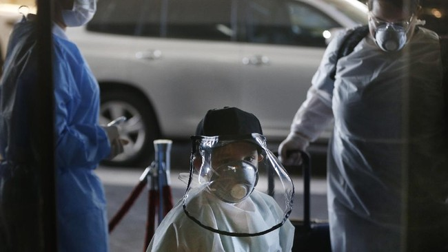 Wearing a face shield and face mask, Matias Morel and his aunt Stefanie Ruiz Diaz, right, pass a temperature check point upon arrival for a flight to Miami, Florida, from Silvio Pettirossi airport in Luque, on the outskirts of Asuncion, Paraguay, Thursday, April 23, 2020. Paraguay's government has organized with several other nations to get their nationals home, amid a lack of flights due to the global lockdown to contain the spread of the new coronavirus. (AP Photo/Jorge Saenz)