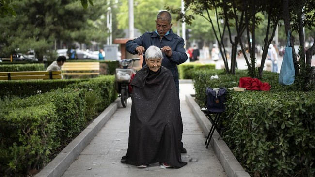 A barber cuts the hair of an elderly woman at a public park in Beijing on May 13, 2020. (Photo by NOEL CELIS / AFP)