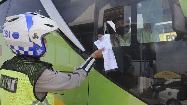 Polisi memeriksa kelengkapan dokumen bus jurusan Jakarta-Madura di pos pemeriksaan Terminal Kargo, Pamekasan, Jawa Timur, Jumat (15/5/2020). Gugus Tugas Percepatan penanganan COVID-19 di kabupaten Pamekasan meningkatkan pemeriksaan kendaraan dari luar kota, pascakebijakan Kementerian Perhubungan terkait beroperasinya kembali semua moda transportasi per Kamis (7/5/2020) lalu. ANTARA FOTO/Saiful Bahri/pras.