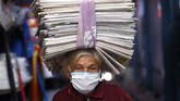 Guillermina de Figueredo, 72, balances recycled newspapers on her head which she sells to merchants who use them as wrappers in Asuncion, Paraguay, Tuesday, May 5, 2020. The government authorized the reopening of some businesses under a plan coined