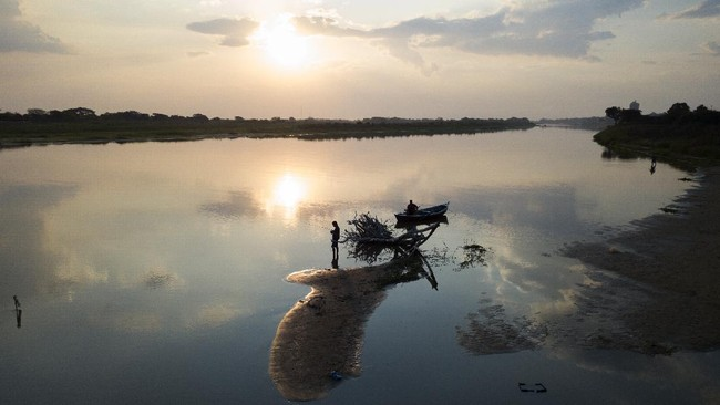 Men fish on the shore of the Paraguay River during a lockdown to prevent spread of the new coronavirus in Lambare, Paraguay, Thursday, April 30, 2020. (AP Photo/Jorge Saenz)