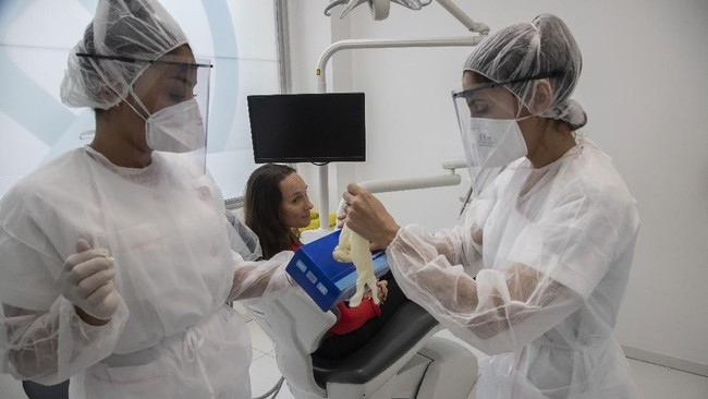 In this Wednesday, May 13, 2020 photo, dental assistant Margot Daussat, left, holds a box with gloves as dentist Sabrine Jendoubi, right, prepares for a dental appointment with patient Veronique Guillot at a dental office in Paris. Those with toothache that suffered through France's two-month lockdown, finally have hope to end the pain. Dental practices are cautiously re-opening and non-emergency dentist appointments are now permitted around the country, as the French government eased confinement restrictions from Monday. (AP Photo/Michel Euler)