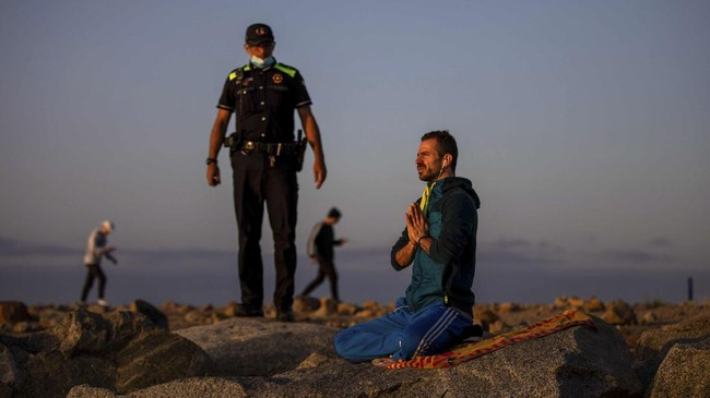 A police officer talks to a man meditating in a beach reopened for sport activities after the lockdown measures imposed by the government in Barcelona, Spain, Friday, May 8, 2020. In last minute negotiations, Spain's government has secured enough parliamentary support to extend later on Wednesday the country's state of emergency. Spain has recorded over 25,600 deaths from the new coronavirus. (AP Photo/Emilio Morenatti)