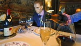 Champagne is poured at a table where mannequins will provide social distancing at the Inn at Little Washington as they prepare to reopen their restaurant Thursday May 14, 2020, in Washington, Va.  The manager say that every other table will have mannequins for social distance guidance when, according to state guidelines, the 5-star restaurant will be allowed reopen on May 29th. (AP Photo/Steve Helber)
