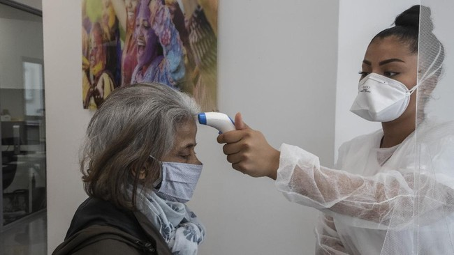 In this Wednesday, May 13, 2020 photo, a masked unidentified patient has her temperature checked by dental assistant Margot Daussat prior to a dental appointment at a dental office in Paris. Those with toothache that suffered through France's two-month lockdown, finally have hope to end the pain. Dental practices are cautiously re-opening and non-emergency dentist appointments are now permitted around the country, as the French government eased confinement restrictions from Monday. (AP Photo/Michel Euler)