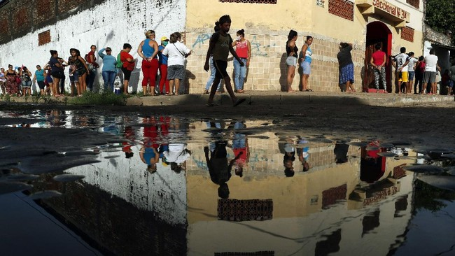 Neighbors line up for free food staples outside Santa Ana primary school in Asuncion, Paraguay, part of an already existing food program through the Education Ministry, as people stay home from work amid the spread of COVID-19, Tuesday, March 31, 2020. (AP Photo/Jorge Saenz)