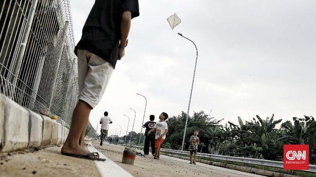 Anak-anak menerbangkan layang-layang di  sebuah lapangan di kawasan Cinere, Jakarta Selatan selama masa pandemi COVID-19 di Indonesia. Jakarta. Jumat (15/5/2020). CNNIndonesia/Andry Novelino