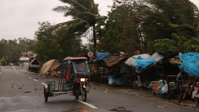 A man drives his tricycle along a road as strong winds caused by typhoon Vongfong hit Catbalogan city, Western Samar province, eastern Philippines, Thursday May, 14, 2020. A strong typhoon slammed into the eastern Philippines on Thursday after authorities evacuated tens of thousands of people while trying to avoid the virus risks of overcrowding emergency shelters. (AP Photo/Simvale Sayat)