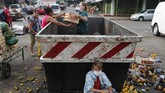 With his family, Fabian Ramirez, 11, scavenges a trash container for discarded vegetables at the