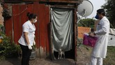 A dog stands in the door of a shack where two Health Ministry workers wait for the occupant to come out to be tested for COVID-19 in Limpio, Paraguay, Wednesday, April 29, 2020. The woman inside was too ill to come to the door, so the nurse entered the home in protective gear to do the test. (AP Photo/Jorge Saenz)