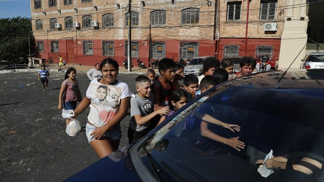 Children reach for food handed out by a woman in a passing car in the poor, Chacarita neighborhood during a lockdown amid the spread of the new coronavirus in Asuncion, Paraguay, Friday, April 10, 2020. (AP Photo/Jorge Saenz)