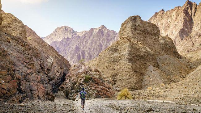 A man is hiking through a wadi in Hajar Mountains near Hatta, UAE