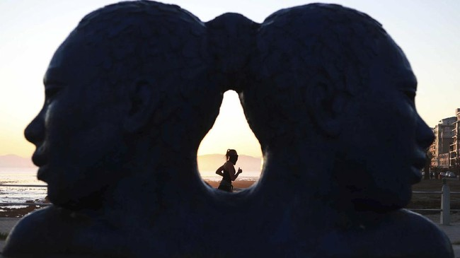 A woman is seen exercising through a sculpture on the promenade in Sea Point, Cape Town South Africa, Saturday, May 9, 2020 as the government continued a phased easing of its strict lockdown measures in a bid to prevent the spread of new coronavirus. (AP Photo/Nardus Engelbrecht)
