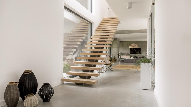 Modern two floor apartment with wooden stairs and living room open to kitchen