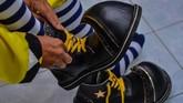 Pegiat badut sulap Mr Arian Maestro bersiap memakai sepatu badut sebelum memainkan trik dalam permainan sulap melalui platform media sosial Facebook di rumahnya, Bumi Resik Panglayungan, Kota Tasikmalaya, Jawa Barat.