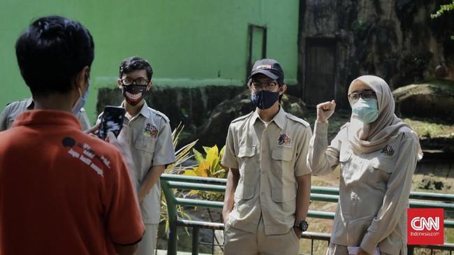 Sejumlah pawang mengamati polah harimau sumatera saat proses pengambilan gambar video untuk siaran langsung melalui media sosial di Taman Margasatwa Ragunan, Jakarta, Minggu (17/5/2020). Siaran langsung polah dua harimau bernama Hana dan Tino itu bertujuan untuk memberikan wawasan tentang satwa dan hiburan kepada masyarakat selama masa pandemi COVID-19. CNN Indonesia/Adhi Wicaksono