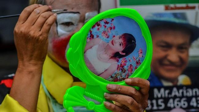 Pegiat badut sulap Mr Arian Maestro merias wajahnya sebelum memainkan trik dalam permainan sulap melalui platform media sosial Facebook di rumahnya, Bumi Resik Panglayungan, Kota Tasikmalaya, Jawa Barat.