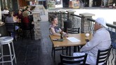 In this Thursday, May 14, 2020 photo, Sara Crane and James Hall, both of Henderson, dine outside at Hennessey's Tavern at the Fremont Street Experience in downtown Las Vegas. The business moved tables to the sidewalk in front of the restaurant after The City of Las Vegas temporarily allowed outdoor dining on public sidewalks. (K.M. Cannon/Las Vegas Review-Journal via AP)