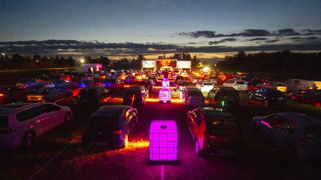 People celebrate a party in their cars during a car disco event playing house music in Altenburg, Germany, Saturday, May 16, 2020. Due to the coronavirus pandemic, major events are restricted and the car disco is an alternative that people enjoy. Up to 250 cars are allowed on the premises and people can celebrate until 1 a.m.  (AP Photo/Jens Meyer)