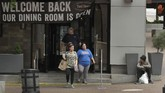 People exit a reopened restaurant Friday, May 15, 2020, in downtown Kansas City, Mo. Restaurants were allowed to serve dine-in customers Friday for the first time since mid-March when the city issued stay-at-home orders to slow the spread of COVID-19. (AP Photo/Charlie Riedel)