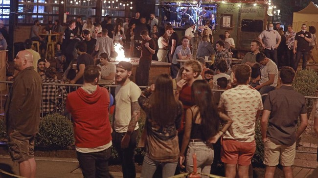 A crowd gathers to drink at Standard Hall, a bar, on Friday, May 15, 2020 in Columbus, Ohio.  Ohio restaurants have the option beginning Friday to offer outdoor dining, the next step toward resuming normal business operations under Republican Gov. Mike DeWine's state reopening plan during the coronavirus pandemic. The bar's owners, Corso Ventures, told WBNS-TV