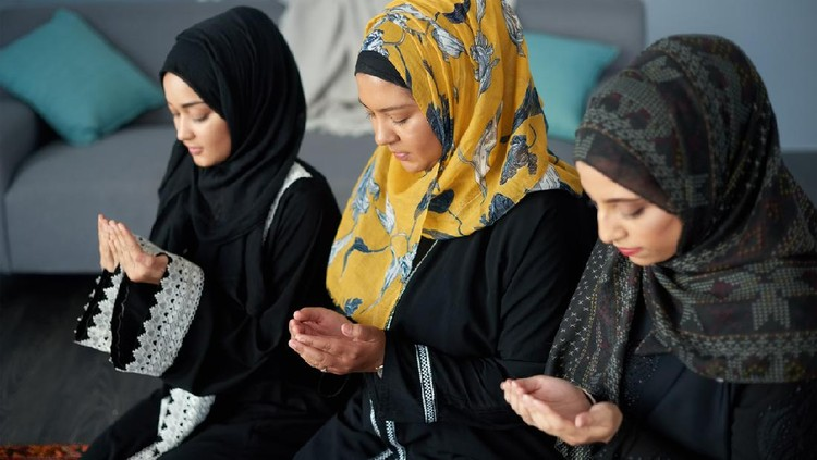 Shot of a group of young muslim women praying together indoors