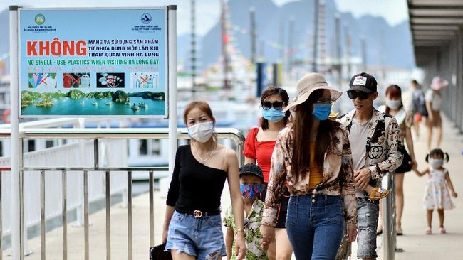 Local tourists wearing face masks leave a pier after returning from a cruise trip in the waters of Ha Long Bay in northeastern province of Quang Ninh on May 16, 2020. (Photo by Manan VATSYAYANA / AFP)