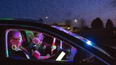 People celebrate a party in their car during a car disco event playing house music in Altenburg, Germany, Saturday, May 16, 2020. Due to the coronavirus pandemic, major events are restricted and the car disco is an alternative that people enjoy. Up to 250 cars are allowed on the premises and people can celebrate until 1 a.m.   (AP Photo/Jens Meyer)
