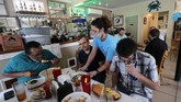 Waitress Gina Lauricella serves customers indoors, for the first time since the state shutdown, at Charles Seafood Restaurant in Harahan, La., Friday, May 15, 2020. Once a hot spot for coronavirus infections, Louisiana is officially easing up Friday on economically devastating business closures and public gathering restrictions that Gov. John Bel Edwards credits with slowing the spread of the virus.   (AP Photo/Gerald Herbert)