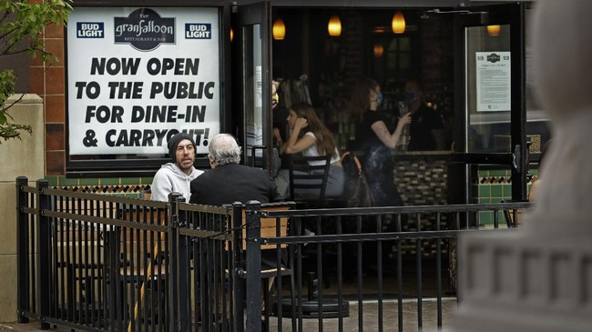 People gather at a restaurant in the Country Club Plaza shopping district Friday, May 15, 2020 in Kansas City, Mo. Restaurants were allowed to serve dine-in customers today for the first time since mid-March when the city issued stay-at-home orders to stream the spread of COVID-19. (AP Photo/Charlie Riedel)