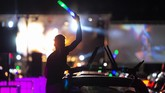 A man celebrates outside his car window during a car disco event playing house music in Altenburg, Germany, Saturday, May 16, 2020. Due to the coronavirus pandemic, major events are restricted and the car disco is an alternative that people enjoy. Up to 250 cars are allowed on the premises and people can celebrate until 1 a.m.   (AP Photo/Jens Meyer)