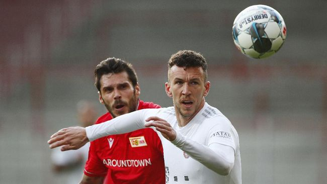 Bayern Munich's Ivan Perisic, right, in action with FC Union Berlin's Christopher Trimmel during the German Bundesliga soccer match between Union Berlin and Bayern Munich in Berlin, Germany, Sunday, May 17, 2020. The German Bundesliga becomes the world's first major soccer league to resume after a two-month suspension because of the coronavirus pandemic. (AP Photo/Hannibal Hanschke, Pool)