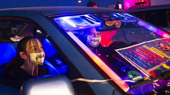 People party in their car during a car disco event playing house music in Altenburg, Germany, Saturday, May 16, 2020. Due to the coronavirus pandemic, major events are restricted and the car disco is an alternative that people enjoy. Up to 250 cars are allowed on the premises and people can celebrate until 1 a.m.  (AP Photo/Jens Meyer)