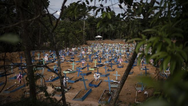 In this May 11, 2020 photo, graves for people who have died in the past month fill a new section of the Nossa Senhora Aparecida cemetery, amid the new coronavirus pandemic, in Manaus, Brazil. Indigenous tribes dwelling up the Solimoes and Negro rivers that merge in Manaus to form the Amazon River tried for weeks to seal their reserves off from the virus, pleading for donations while awaiting government delivery of food assistance so they could remain isolated. It didn't come for many, indigenous advocates said. (AP Photo/Felipe Dana)