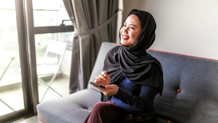 Young beautiful muslim girl with phone in home