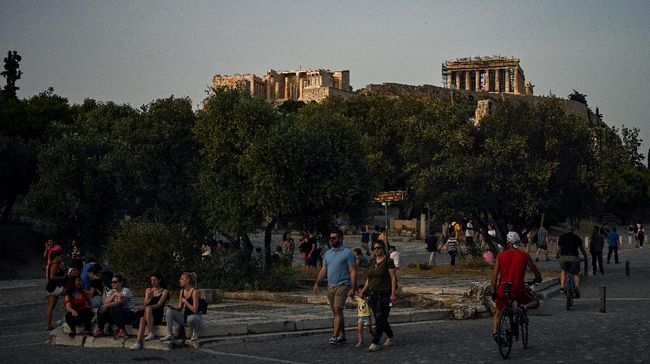 People walk with in background the ancient Temple of Parthenon atop the Acropolis hill in Athens on May 17, 2020 during the gradual deconfinement started on May 4, following a lockdown aimed at curbing the spread of the COVID-19 pandemic, caused by the novel coronavirus. - The Acropolis of Athens, flagship monument of Antiquity, will reopen on May 18, 2020 morning like all archaeological sites in Greece, two months after