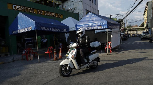 In this May 11, 2020, photo, anesthesiologist Manuel Sotelo III rides his scooter past Ospital ng Sampaloc as he drives home after work at Sampaloc district in Manila, Philippines. Sotelo was tested positive for the COVID-19 disease last month and is now cleared of the virus. Like many health workers, he now lives away from family for fear that he might bring home the virus as he goes back to the frontlines to take care of COVID-19 patients. (AP Photo/Aaron Favila)