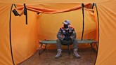 A security guard wearing a protective mask sit inside an isolation tent that will serve as a quarantine facility for people showing symptoms of the COVID-19 at an indoor stadium prepared to become an emergency hospital amid the new coronavirus outbreak in Jakarta, Indonesia, Monday, May 18, 2020. (AP Photo/Tatan Syuflana)