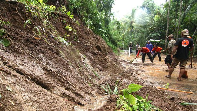 Petugas Badan Penanggulangan Bencana Daerah (BPBD) Banyuwangi membersihkan lumpur yang menutupi jalan akibat longsor di Desa Kluncing, Licin, Banyuwangi, Jawa Timur, Senin (18/5/2020). Tanah longsor di kaki Gunung Ijen yang menyebabkan akses jalan penghubung Desa Pakel dengan Desa Kluncing itu terjadi akibat intensitas hujan deras yang mengguyur kawasan tersebut sejak pagi hingga sore hari. ANTARA FOTO/Budi Candra Setya/pras.