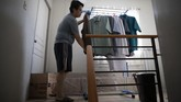 In this May 9, 2020, photo, anesthesiologist Manuel Sotelo III arranges his clothes as he lives alone at their house at San Juan in Manila, Philippines. Sotelo was tested positive for the COVID-19 disease last month and is now cleared of the virus. Like many health workers, he now lives away from family for fear that he might bring home the virus as he goes back to the frontlines to take care of COVID-19 patients. (AP Photo/Aaron Favila)