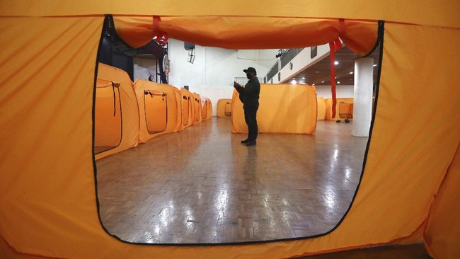 A government official inspect isolation tents that will serve as a quarantine facility for people showing symptoms of the COVID-19 at an indoor stadium prepared to become an emergency hospital amid the new coronavirus outbreak in Jakarta, Indonesia, Monday, May 18, 2020. (AP Photo/Tatan Syuflana)
