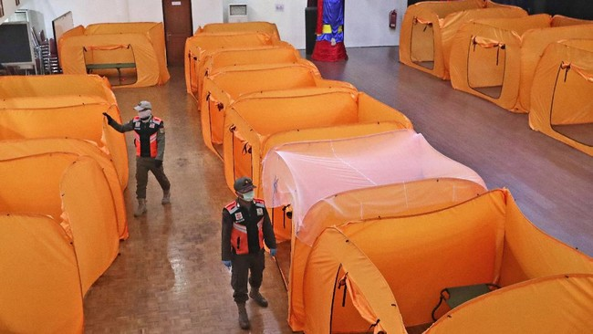 Security guards wearing protective masks inspect isolation tents that will serve as a quarantine facility for people showing symptoms of the COVID-19 at an indoor stadium prepared to become an emergency hospital amid the new coronavirus outbreak in Jakarta, Indonesia, Monday, May 18, 2020. (AP Photo/Tatan Syuflana)