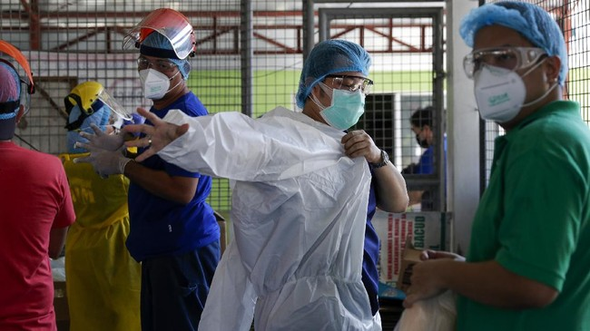 In this May 8, 2020, photo, anesthesiologist Manuel Sotelo III wears a protective suit as they conduct targeted mass testing among residents at Sampaloc district in Manila, Philippines. Sotelo was tested positive for the COVID-19 disease last month and is now cleared of the virus. Like many health workers, he now lives away from family for fear that he might bring home the virus as he goes back to the frontlines to take care of COVID-19 patients. (AP Photo/Aaron Favila)