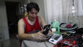 In this May 11, 2020, photo, anesthesiologist Manuel Sotelo III reacts as he talks to his 2-year-old daughter via video call as he lives alone at their house at San Juan in Manila, Philippines. Sotelo was tested positive for the COVID-19 disease last month and is now cleared of the virus. Like many health workers, he now lives away from family for fear that he might bring home the virus as he goes back to the frontlines to take care of COVID-19 patients. (AP Photo/Aaron Favila)