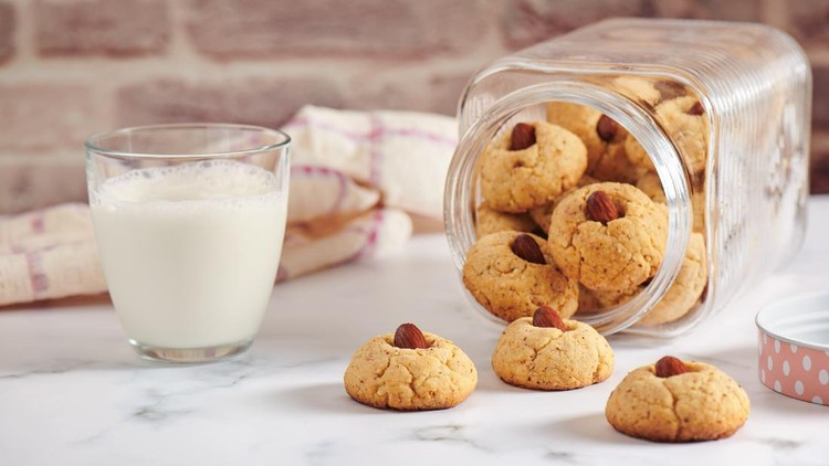 Turned jar with dropped out almond cookies, glass of milk