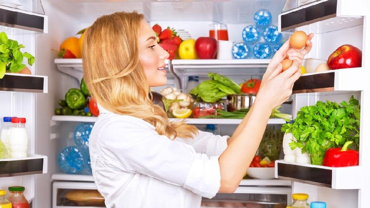 Cute female taking eggs from the fridge, attractive housewife take care about health, fresh tasty organic food, healthy eating concept