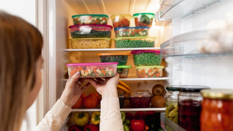 Close up shot of woman taking container with frozen mixed vegetables from refrigerator while looking at camera.