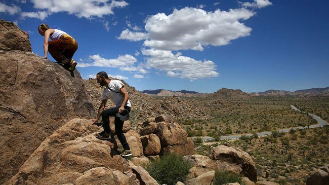 Matilda Fresk, left, and Enosh Baker hike along the rocks at Joshua Tree National Park in California, Tuesday, May 19, 2020. The park reopened this week after a lengthy closure to help slow the spread of the new coronavirus. (AP Photo/Jae C. Hong)